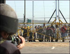Un soldat israélien mettant en joue des manifestants contre l'édification du mur en Cisjordanie