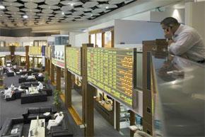 Un investisseur regarde vers le plancher commercial de la Dubai Financial Market pendant les heures d'ouverture à la Dubai World Trade Center. (Photo : www.daylife.com)
