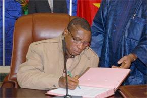 Le chef de la junte guinéenne, le capitaine Moussa Dadis Camara, signe un accord de sortie de crise, à Ouagadougou. (Photo : AFP)