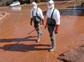 Des Hongrois chargés de nettoyer les rues de Devecser remplies de boue rouge. (Photo : AFP)