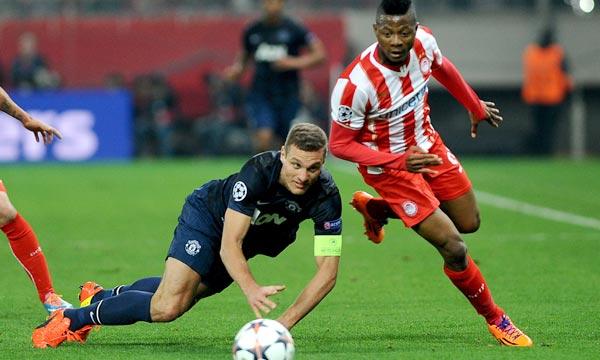 Le défenseur serbe de Manchester United, Nemanja Vidic, tombe sous les yeux de l'attaquant nigérian de l'Olympiakos du Pirée, Michael Olaitan, en 8e de finale aller de la Ligue des champions, à Athènes. Ph  : AFP