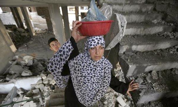 Une femme palestinienne se rend dans sa maison détruite après une frappe israélienne, à Gaza. Les hostilités ont fait 166 morts et 1.120 blessés, en majorité des civils palestiniens, depuis le début de l'opération militaire «Bordure protectrice». Ph