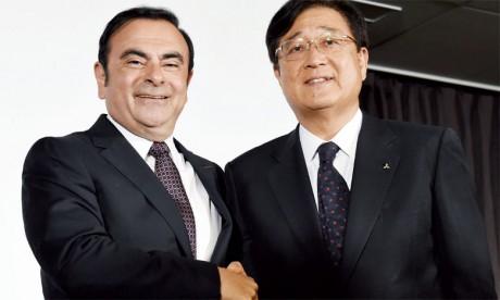 Le PDG de Renault et de Nissan, Carlos Ghosn, serrant la main au patron de Mitsubishi, Osamu Masuko.Ph. AFP