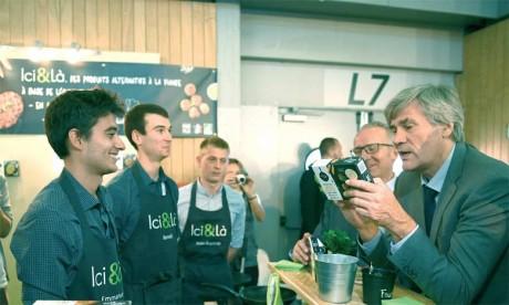 Le ministre de l'Agriculture Stephane Le Foll (à droite) sur le stand de la société «Ici et là», lancée notamment par Emmanuel Brehier (2e à partir  de la gauche), au SIAL le 16 octobre2016.