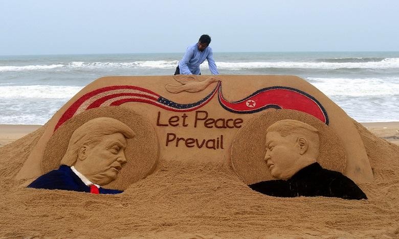 L'artiste Sudarshan Pattnaik termine une sculpture de sable représentant le président américain Donald Trump et le dirigeant nord-coréen Kim Jong Un le 11 juin 2018, avant le sommet de Singapour. Ph. AFP