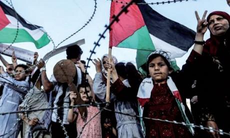 Entre drapeaux et barbelés, un enfant palestinien tenant une clé en bois symbolisant le retour, à la frontière entre la Bande de Gaza et Israël.                        Ph. AFP.