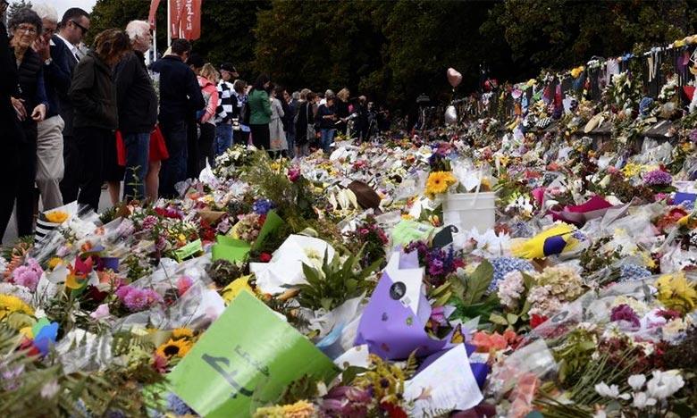 Les gens regardent les hommages rendus au Jardin botanique de Christchurch. Le gouvernement va mettre en place un programme de rachat des armes interdites et une période d'amnistie pour leurs propriétaires. Ph : AFP