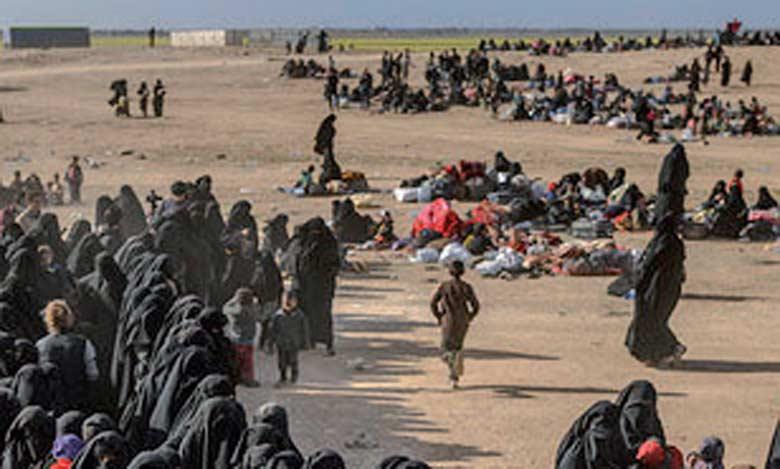 Des personnes attendent d'être fouillés par les Forces démocratiques syriennes après avoir quitté le dernier réduit de daech, à Baghouz, dans l'est de la Syrie.  Ph. AFP.