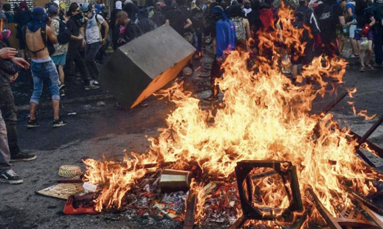 Des manifestants allumant un bûcher à Santiago lors de protestations anti-gouvernementales et de la commémoration de la mort d'un Mapuche tué par la police un an auparavant.       Ph. AFP
