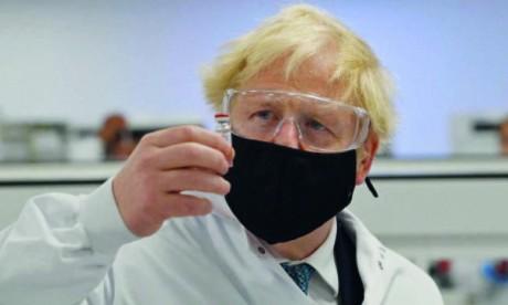 Le Premier ministre Boris Johnson examinant un flacon du vaccin AstraZeneca, à l'usine de fabrication pharmaceutique de Wockhardt à Wrexham, au nord du Pays de Galles.  Ph. AFP