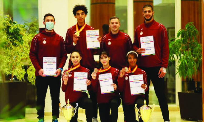 Les taekwondoïstes de l'équipe nationale arborant leurs médailles  en compagnie de leur entraîneur, David Sicot.